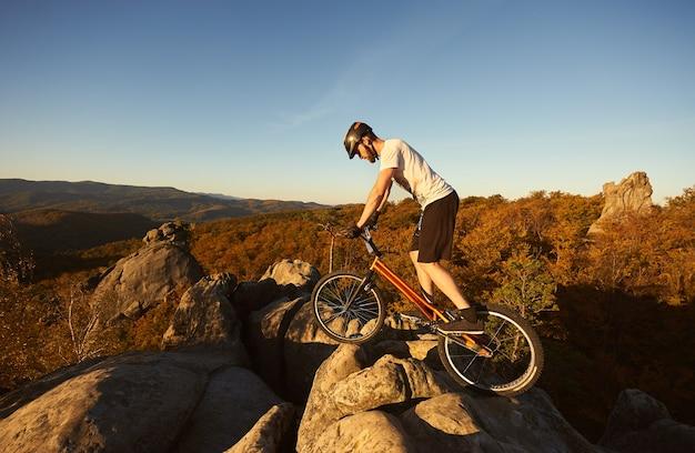 Profesjonalny rowerzysta balansujący na rowerze próbnym o zachodzie słońca