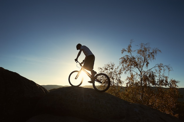Profesjonalny rowerzysta balansujący na rowerze trialowym o zachodzie słońca