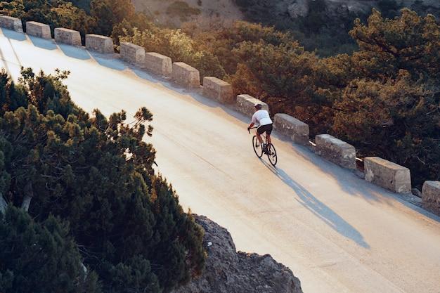 Profesjonalny rowerzysta na górskiej drodze o wschodzie słońca