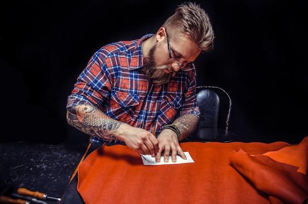 Profesjonalny rzemieślnik wykonujący galanterię skórzaną w swoim sklepie / napis leather tanner z galanterią skórzaną w swoim studio.