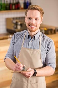 Profesjonalny serwis. szczęśliwy radosny miły człowiek uśmiecha się i pisze notatki podczas pracy jako kelner w kawiarni