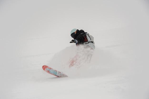 Profesjonalny snowboardzista jedzie po czystym górskim stoku w proszku