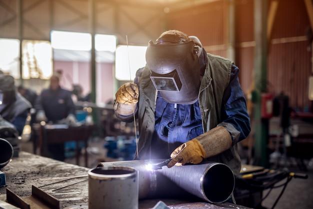 Profesjonalny spawacz w mundurze ochronnym i masce zgrzewający metalową rurę na stole przemysłowym z innymi pracownikami z tyłu w warsztacie przemysłowym.