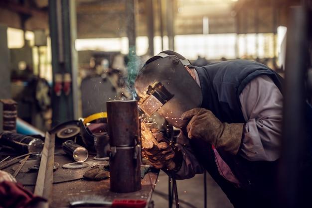 Profesjonalny spawacz w mundurze ochronnym i masce zgrzewający rurę metalową na stole przemysłowym z innymi narzędziami w warsztacie przemysłowym.