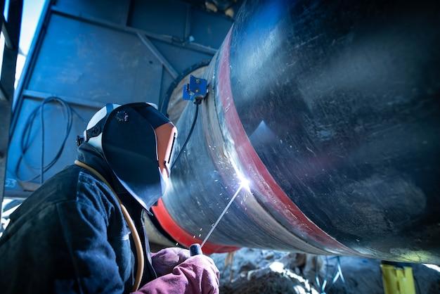 Profesjonalny spawacz zgrzewający rurę na konstrukcji rurociągowej