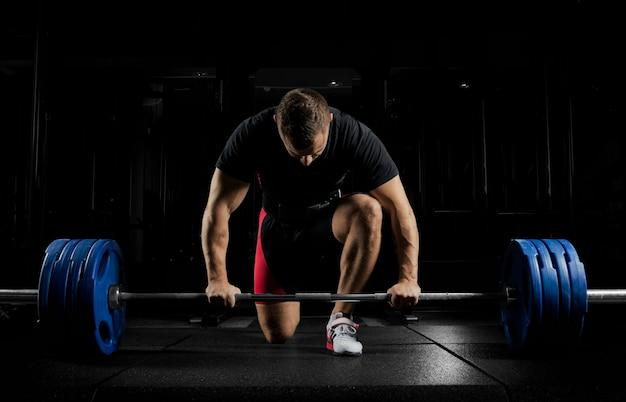 Profesjonalny sportowiec pochylił się nad sztangą i przygotowuje się do podniesienia bardzo dużego ciężaru.