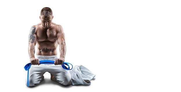 Profesjonalny sportowiec siedzi na siłowni w kimono z niebieskim paskiem. koncepcja karate, jiu-jitsu, sambo, judo. różne środki przekazu