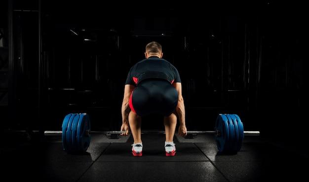 Profesjonalny sportowiec siedzi przed drążkiem i przygotowuje się do jego podniesienia.