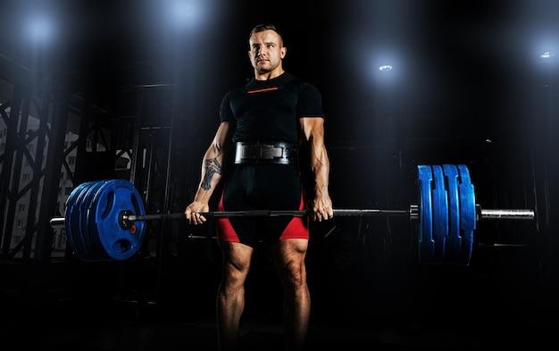 Profesjonalny sportowiec stoi i trzyma bardzo ciężką sztangę.
