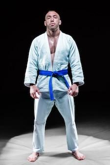 Profesjonalny sportowiec stoi na siłowni w kimono z niebieskim paskiem. koncepcja karate, jiu-jitsu, sambo, judo. różne środki przekazu