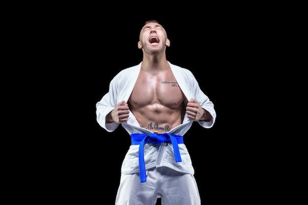Profesjonalny sportowiec w kimonie krzyczy emocjonalnie. koncepcja karate, jiu-jitsu, sambo, judo. różne środki przekazu