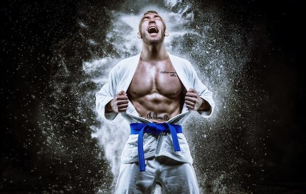 Profesjonalny sportowiec w kimonie krzyczy emocjonalnie. pojęcie zawodów karate i judo. różne środki przekazu