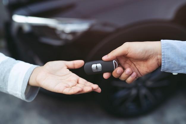 Profesjonalny sprzedawca wręczanie kluczy nowemu właścicielowi samochodu. wypożyczalnia samochodów. ubezpieczenie samochodu w salonie, kobiety podczas pracy z klientem w salonie samochodowym.