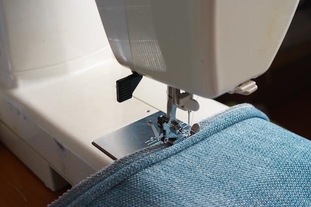 Profesjonalny sprzęt. nowoczesna maszyna do szycia ze specjalną stopką dociskową. proces szycia ozdobnego lamówki niebieskiej części garderoby.