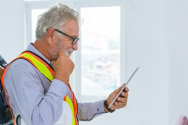 Profesjonalny starszy inżynier usign tablet i gest myślenia