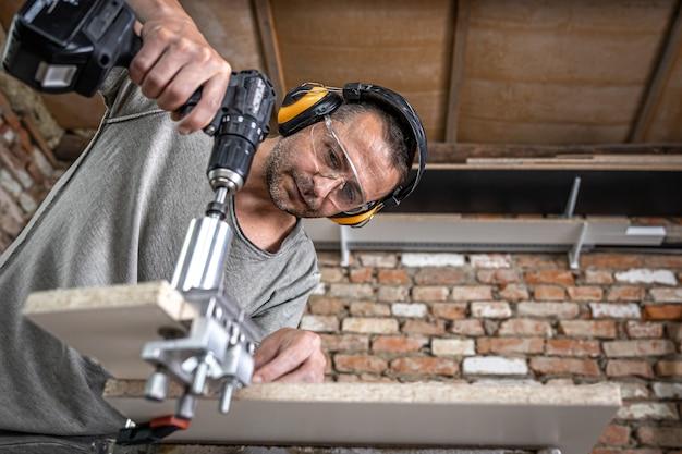 Profesjonalny stolarz pracujący z drewnem i narzędziami budowlanymi w domu.