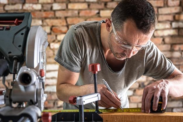 Profesjonalny stolarz pracuje w warsztacie piłą tarczową ukośnicą.
