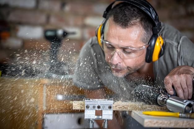 Profesjonalny stolarz w trakcie wiercenia w drewnie wydmuchuje resztę drewna.