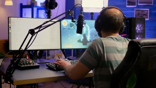 Profesjonalny streamer e-sportowy korzystający ze słuchawek i rozmawiający z zespołem na temat serwisów streamingowych podczas zawodów w kosmicznych strzelankach