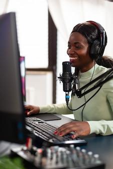 Profesjonalny streamer e-sportowy rozmawiający z kolegami z drużyny podczas turnieju na żywo. streamuj wirusowe gry wideo dla zabawy przy użyciu słuchawek i klawiatury podczas mistrzostw online.