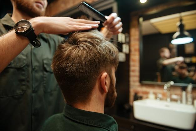 Profesjonalny stylista strzygł włosy swojego klienta. widok z tyłu.