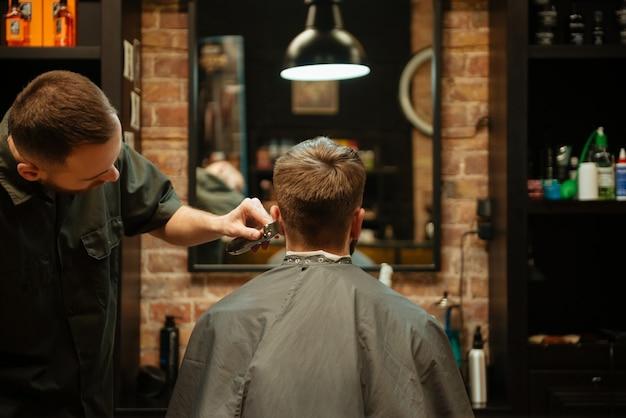 Profesjonalny stylista strzygł włosy swojego klienta.