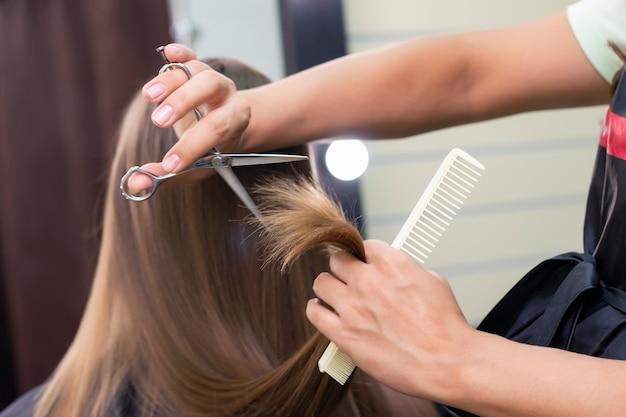 Profesjonalny stylista tnie kobiece włosy w salonie