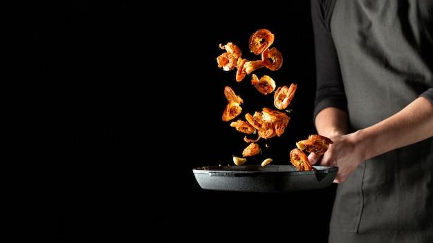 Profesjonalny szef kuchni przygotowuje krewetki lub langusty