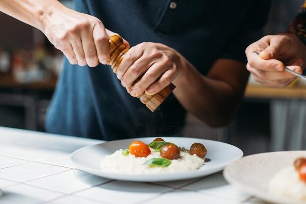 Profesjonalny szef kuchni przygotowuje niesamowite, smaczne parujące danie z włoskiego risotto z parmezanem w designerskiej kuchni hipster