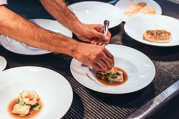 Profesjonalny szef kuchni serwujący jedzenie na talerzach