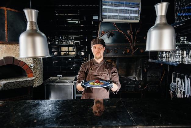 Profesjonalny szef kuchni serwuje świeżo przygotowaną sałatkę z pomidorów i zieleniny cielęcej z sosem w wykwintnej restauracji.