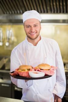 Profesjonalny szef kuchni trzyma hamburgery w talerzu
