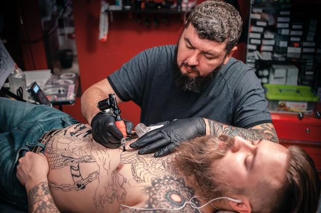 Profesjonalny tatuator pokazujący proces tworzenia tatuażu w studio tatuażu