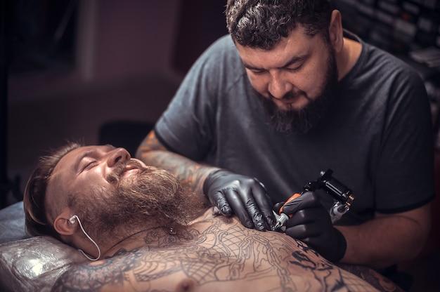 Profesjonalny tatuator pokazuje proces wykonywania tatuażu w studio.
