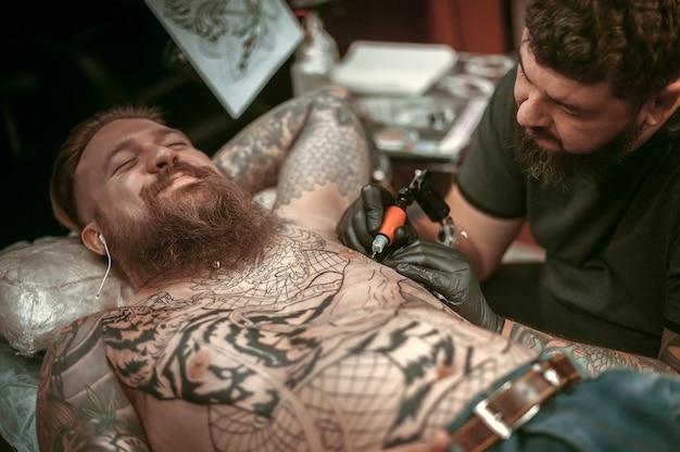 Profesjonalny tatuażysta demonstruje proces wykonywania tatuażu.