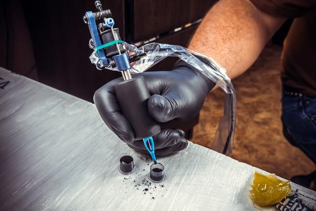 Profesjonalny tatuażysta przedstawiający proces tworzenia tatuażu w studio.