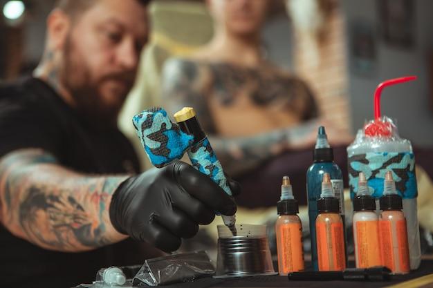 Profesjonalny tatuażysta robi nowy tatuaż dla swojego klienta