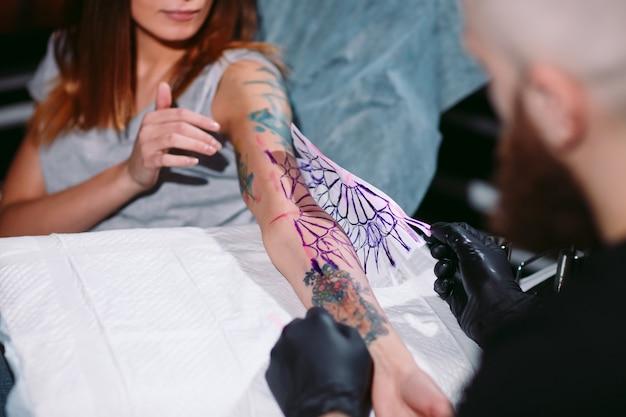 Profesjonalny tatuażysta wykonuje tatuaż na dziewczynie.