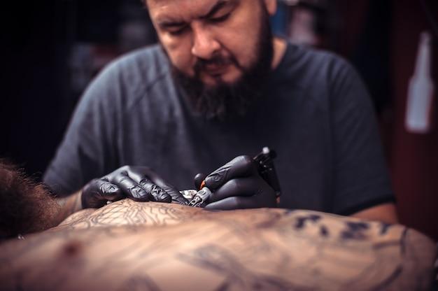 Profesjonalny tatuażysta wykonuje tatuaż w pracowni warsztatowej