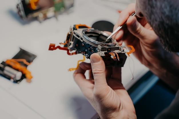 Profesjonalny technik naprawia zepsuty aparat cyfrowy, stawia w centrum serwisowym lub warsztacie