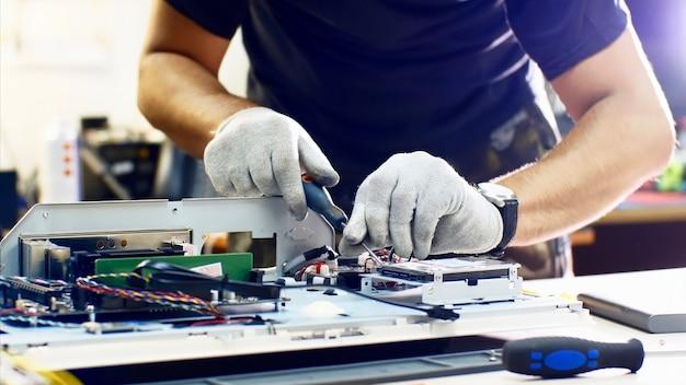 Profesjonalny technik odpina dysk twardy monoblok naprawiając go w warsztacie.