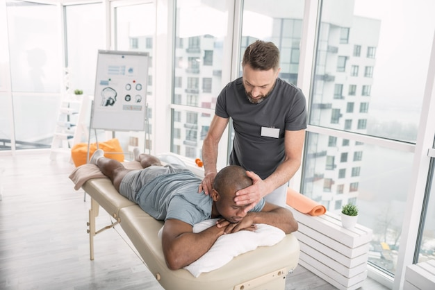 Profesjonalny terapeuta. bystry, wykwalifikowany mężczyzna trzymający głowę pacjenta podczas pracy jako terapeuta w centrum rehabilitacji
