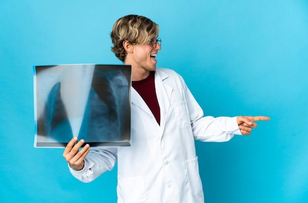 Profesjonalny traumatolog mężczyzna wskazując palcem w bok i przedstawiając produkt
