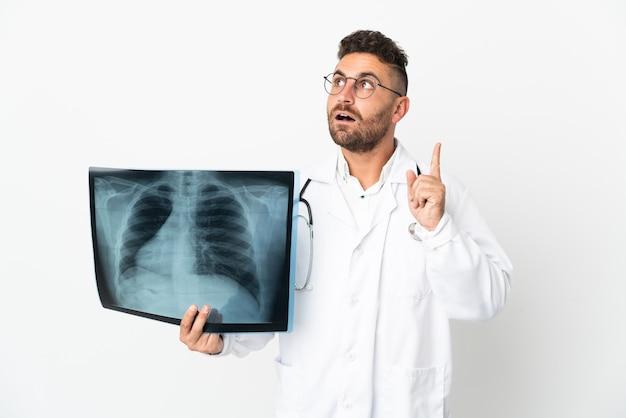 Profesjonalny traumatolog na białym tle myślący o pomyśle wskazującym palec w górę