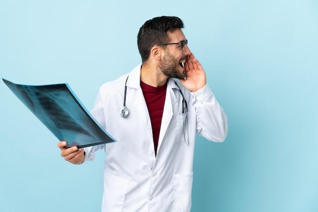 Profesjonalny traumatolog trzymający radiografię izolowaną na niebieskiej ścianie krzyczący z szeroko otwartymi ustami