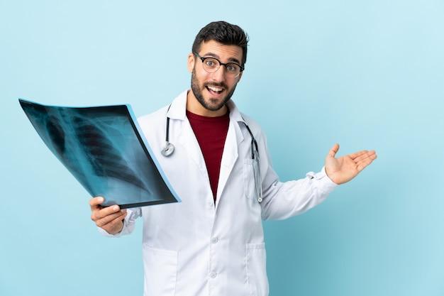 Profesjonalny traumatolog trzymający radiografię na niebiesko wyciągających ręce na bok, aby zaprosić do siebie