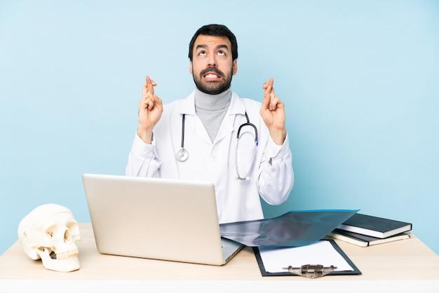 Profesjonalny traumatolog w miejscu pracy ze skrzyżowanymi palcami i życzeniami wszystkiego najlepszego