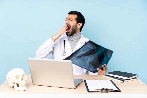 Profesjonalny traumatolog w miejscu pracy ziewający i zakrywający dłonią szeroko otwarte usta