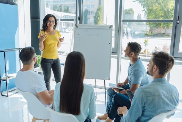 Profesjonalny trener biznesu. pozytywnie zachwyciła inteligentną kobietę patrząc na swoją grupę i prezentując swój wykład, jednocześnie dzieląc się swoim osobistym doświadczeniem