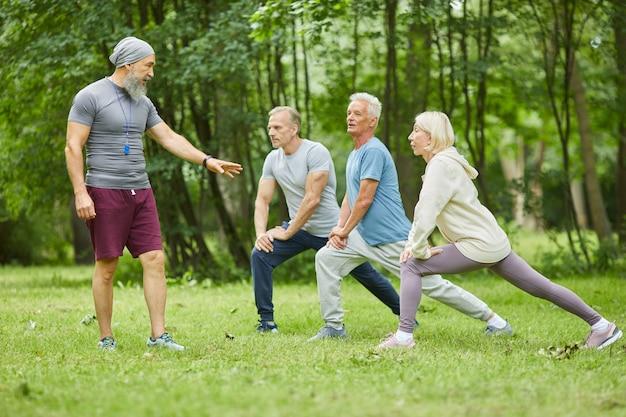 Profesjonalny trener fitness pracujący w parku miejskim z aktywnymi osobami starszymi, korygujący je podczas wykonywania ćwiczeń